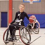 Bild på ung tjej som spelar rullstolsbasket och använder Mollii